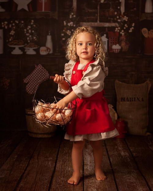 Niña vestida de navidad con huevos en la cocina