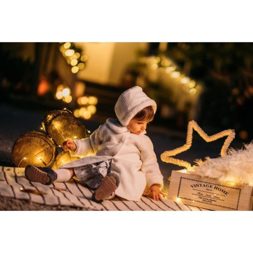 Niño pequeño entre adornos Navidad
