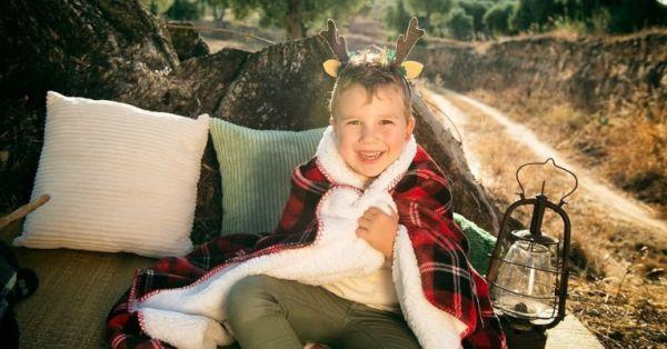 Niño envuelto en manta navideña, con orejas de reno