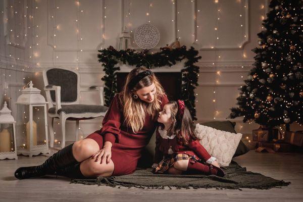 Madre e hija delante de la chimenea en Navidad