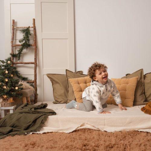 Niño riendo entre cojines en Navidad