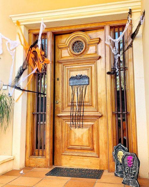 Puerta decorada con telarañas y lápidas halloween
