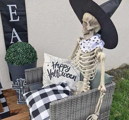 Esqueleto de brujo sentado en sillón Halloween