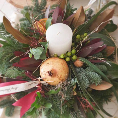 Centro de mesa de navidad con vela blanca, granada, nueces y otros elementos