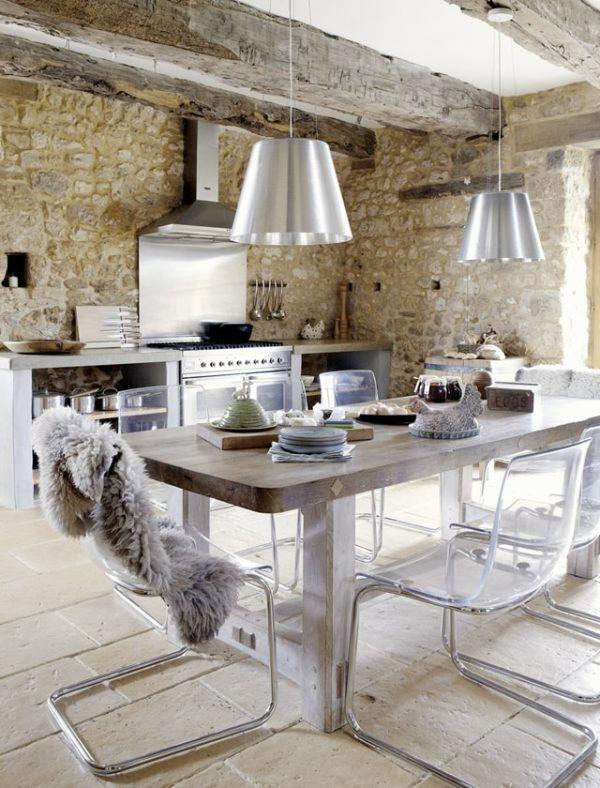 Cocina estilo industrial con lámparas de acero y pared de piedra