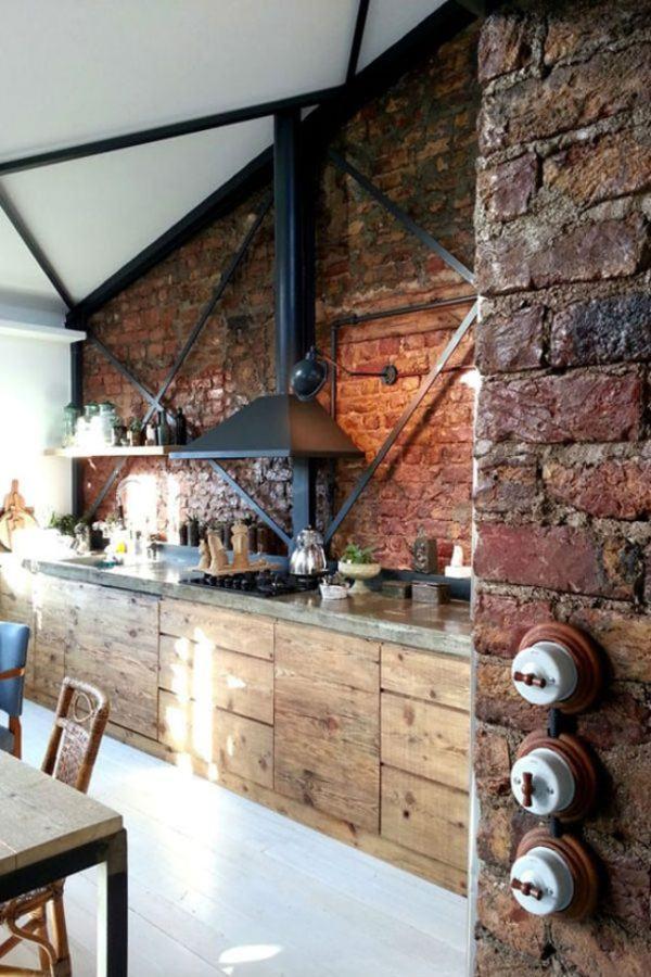 Cocina industrial con muebles de madera y pared de ladrillo con mucha luz