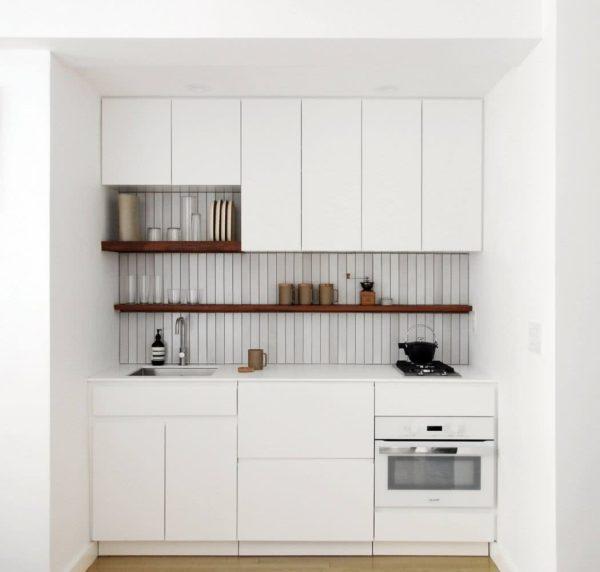 Cocina pequeña alargada blanca con estante de madera