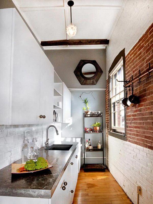 Cocina pequeña y alargada con pared de ladrillo marrón