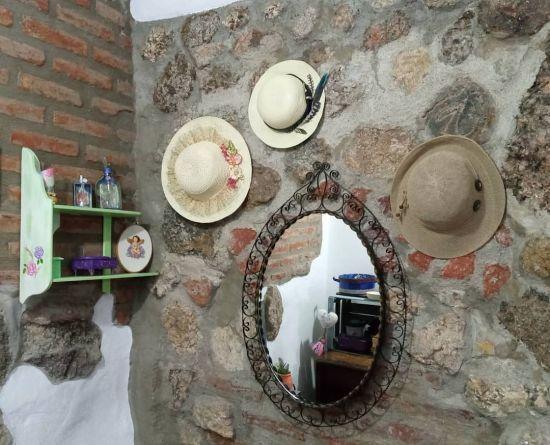 Pared de piedras con espejo y sombreros