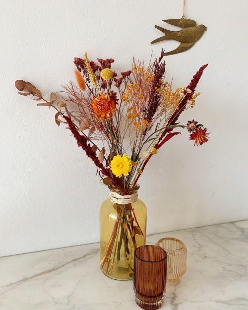 Jarrón de flores secas con vasos en dorado y cobre